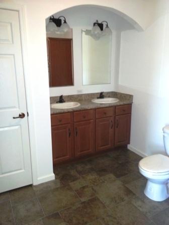 Double sinks, linen closet in master bath.