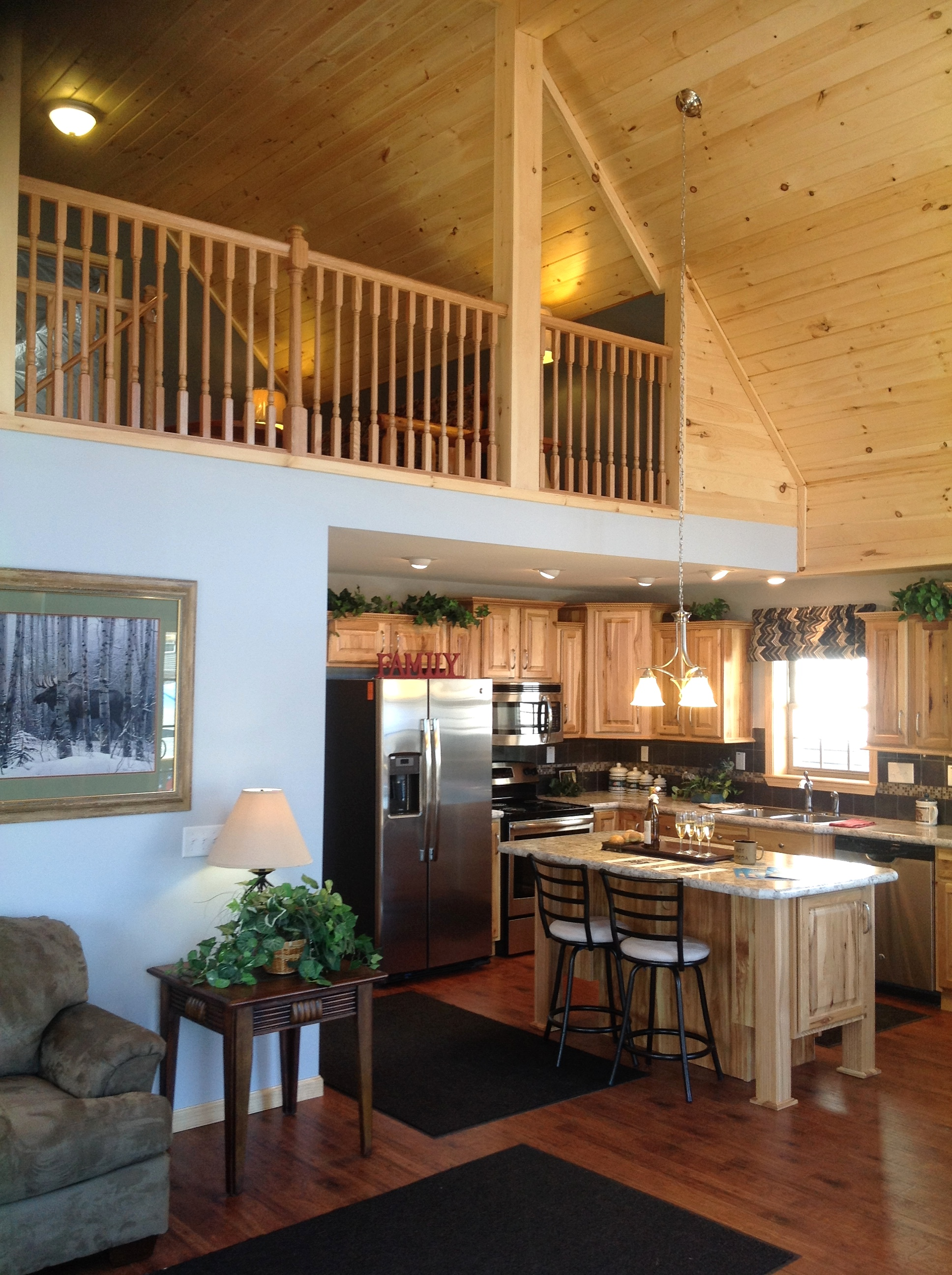 Vaulted loft with pine railing, overlooking kitchen.