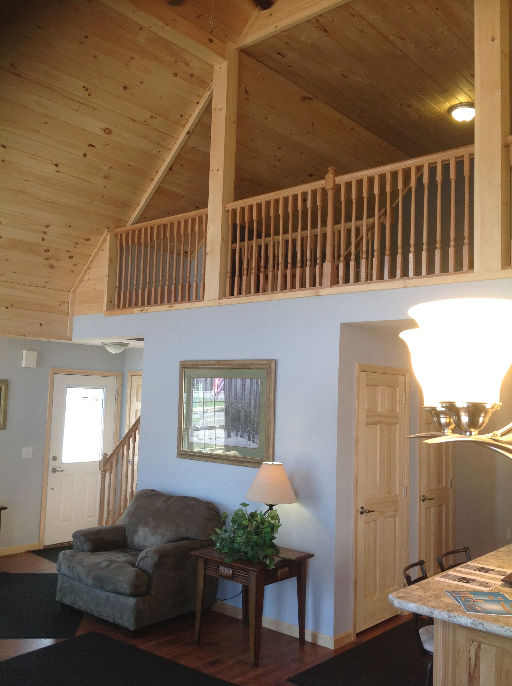 Vaulted loft with pine railing, overlooking living area.